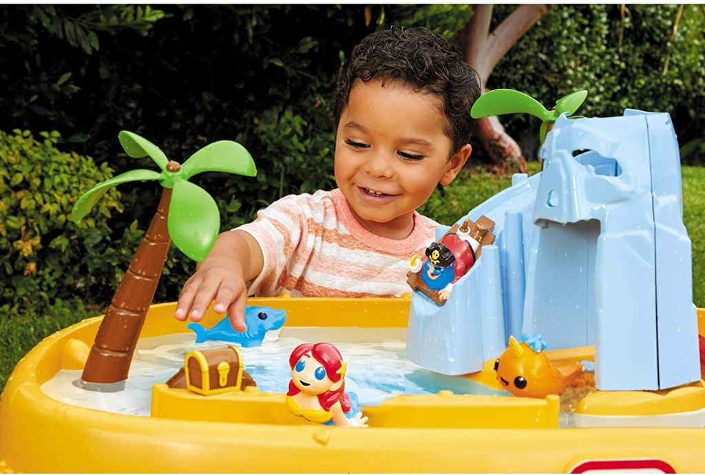 boy playing with characters on Little Tikes Sea Table