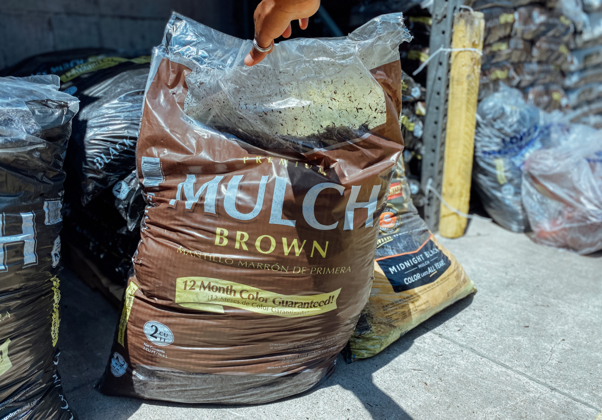 hand holding up large bag of mulch