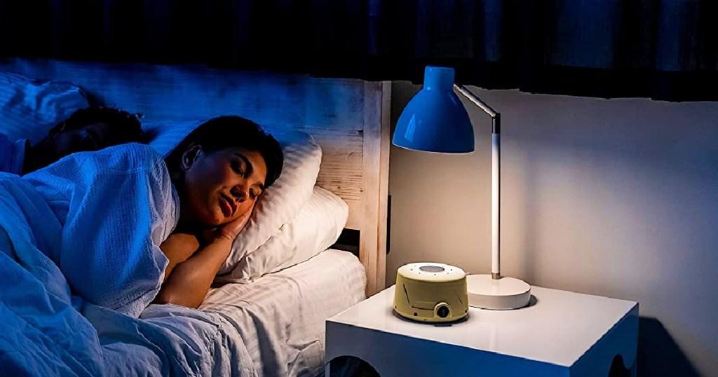 woman sleeping next to a white noise machine