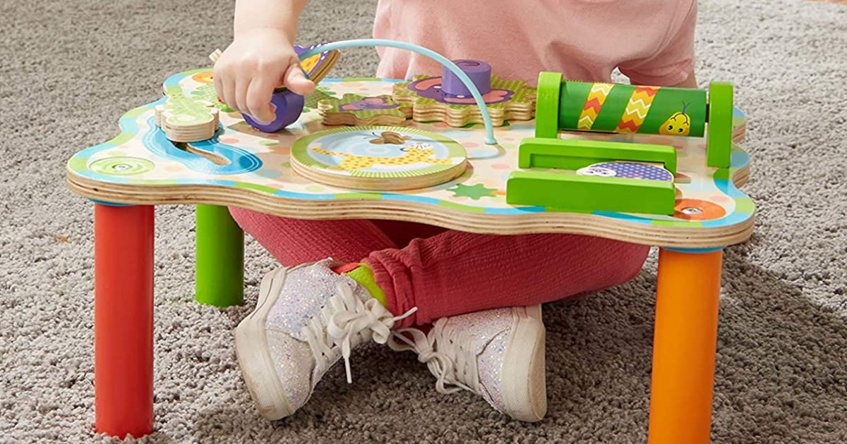 Child on the floor sitting with table playset