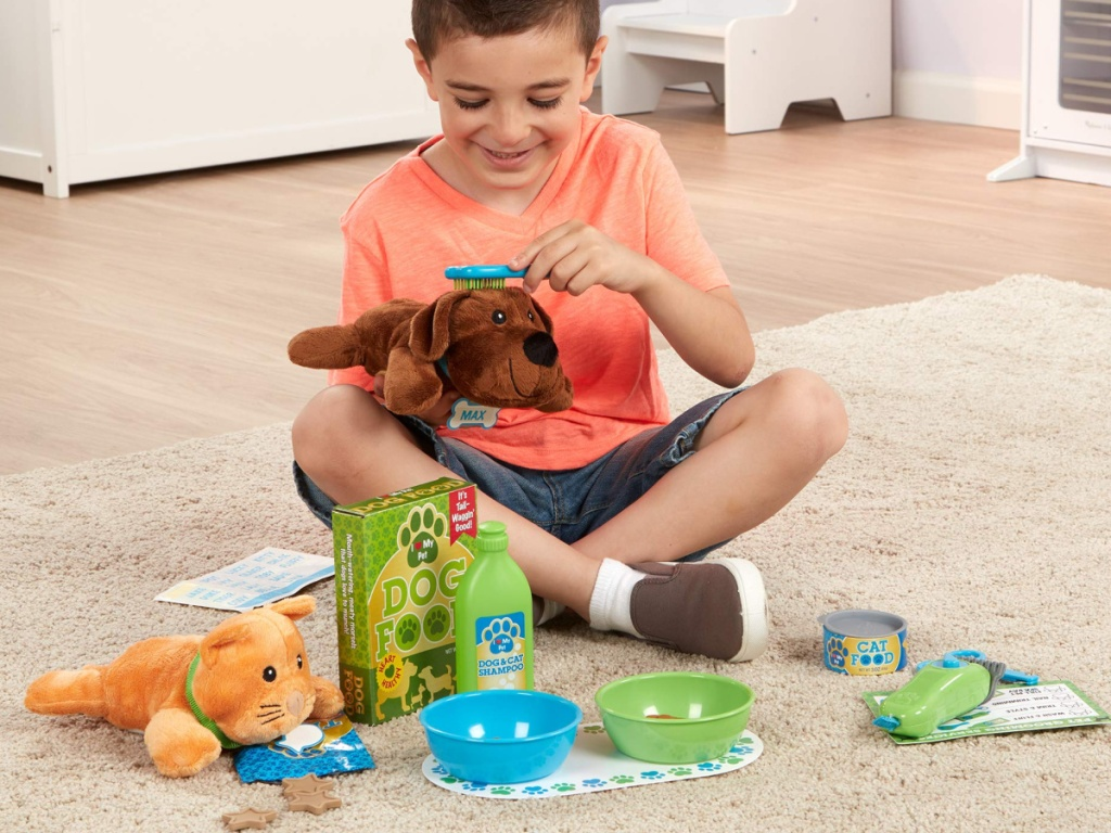 boy sitting on the floor playing with melissa and doug grooming set