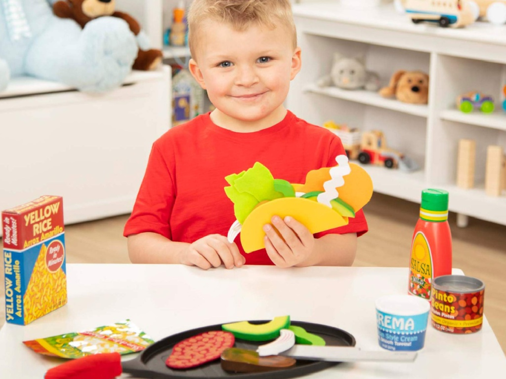 little boy playing with a melissa and doug tortilla set