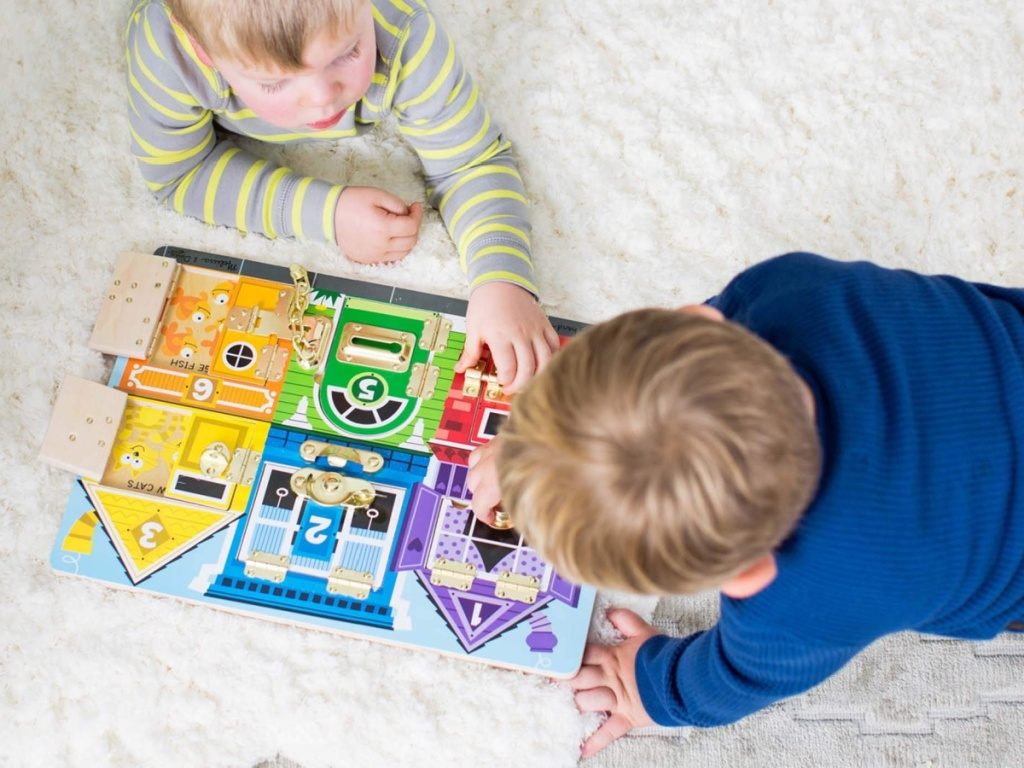 2 toddlers laying on the floor playing with melissa and doug latch puzzle set