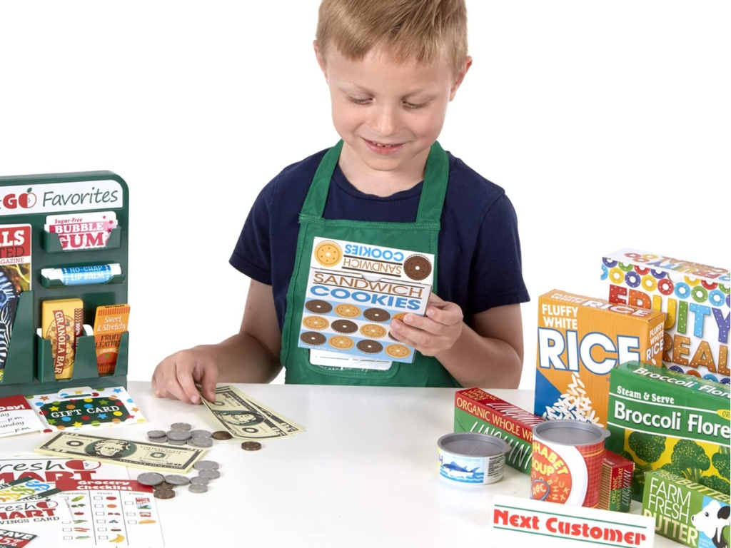 boy surrounded by melissa and doug toy food