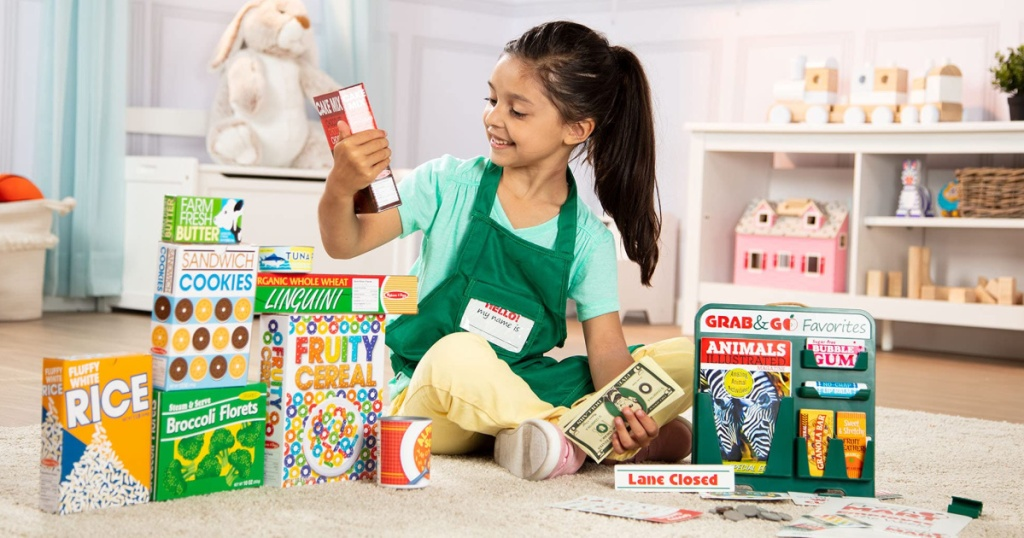 girl sitting on the floor with melissa and doug play store food