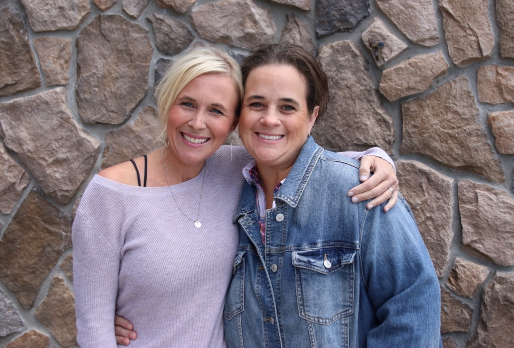 two woman holding each other smiling in front of stone wall