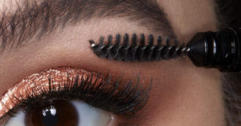 woman using NYX Brow pencil on eyebrow