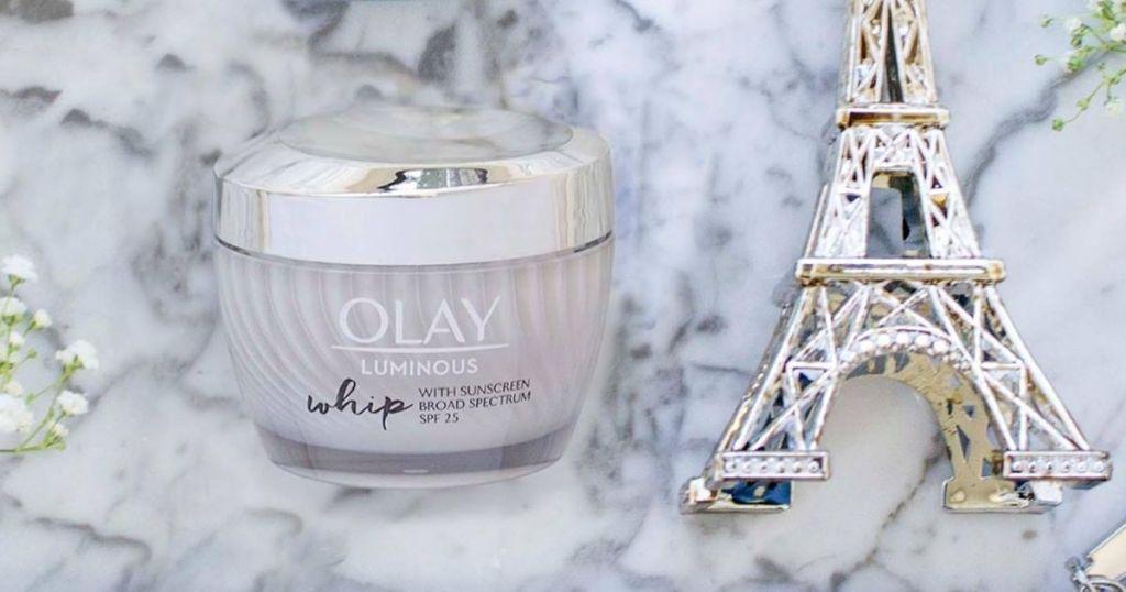 Olay moisturizer next to a mini eiffel tower