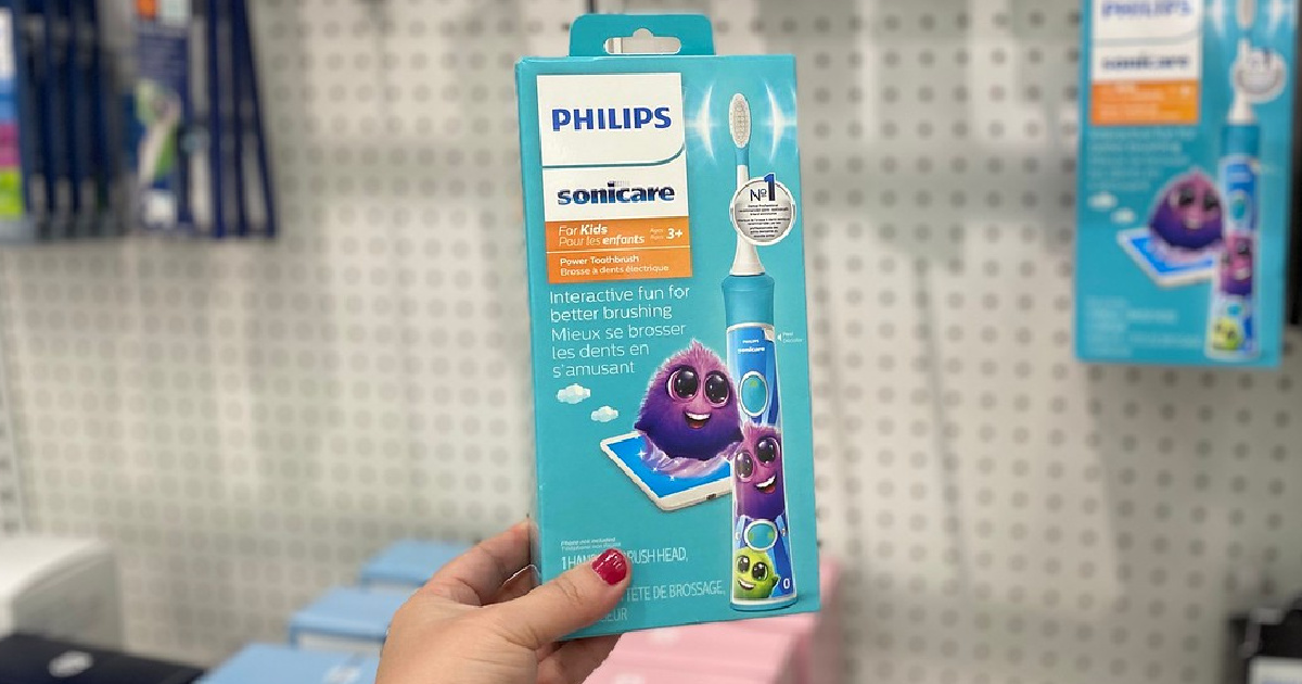hand holding up a sonicare kids electric toothbrush in a store