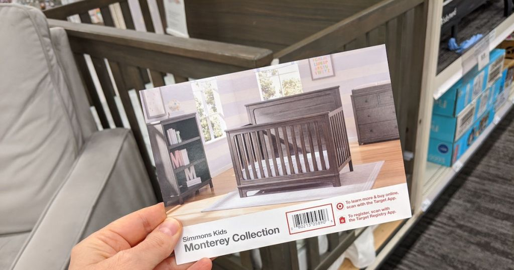 hand holding picture of crib