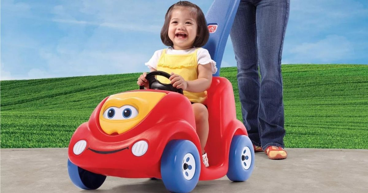 girl riding in a push buggy toy