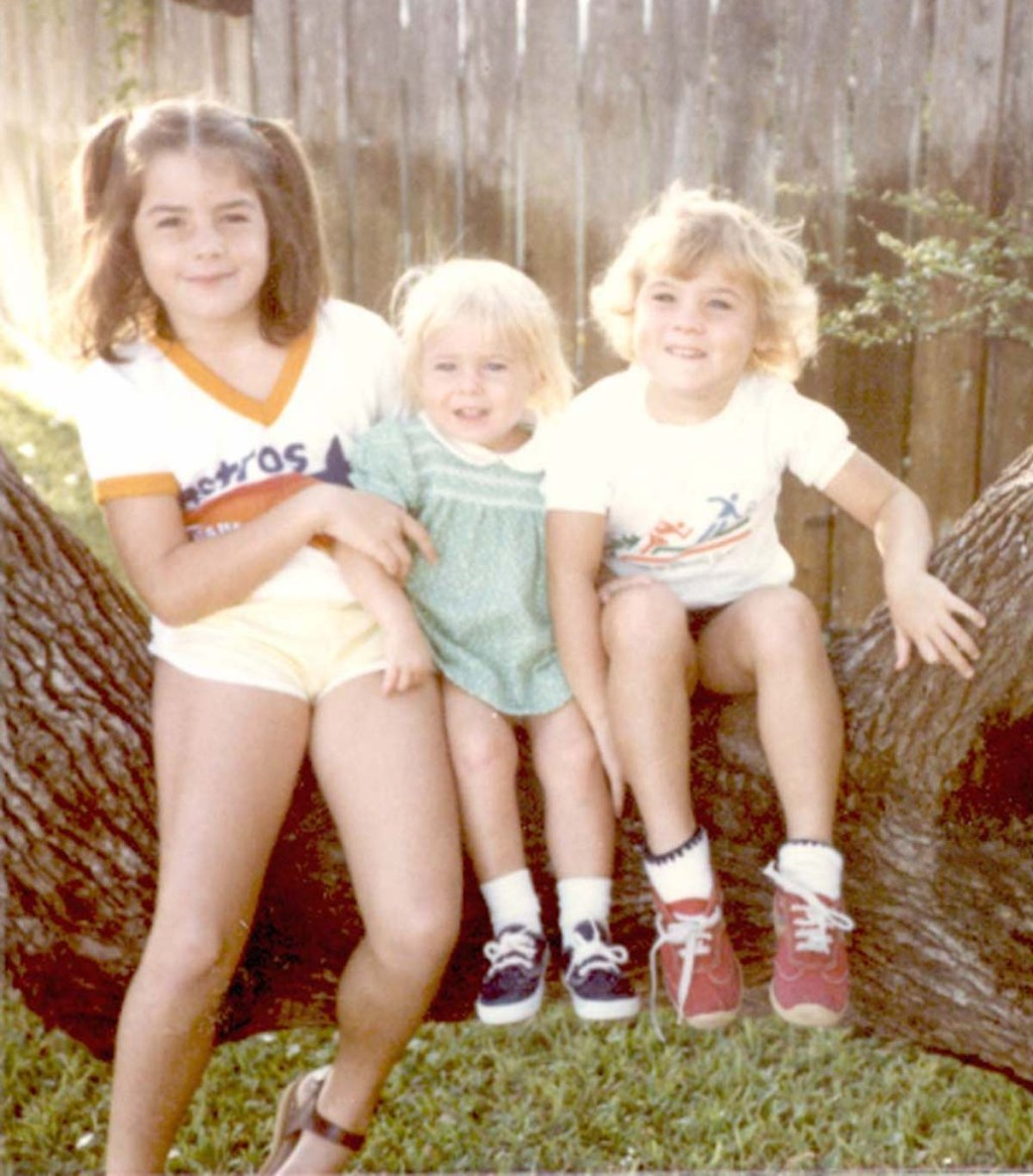 old picture of three kids sitting on tree