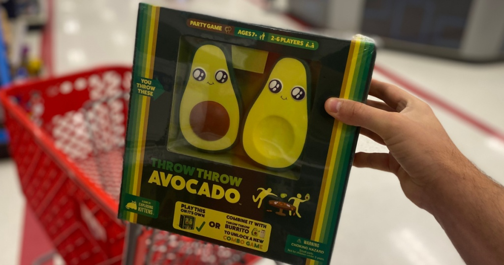 hand holding board game with an avocado on front