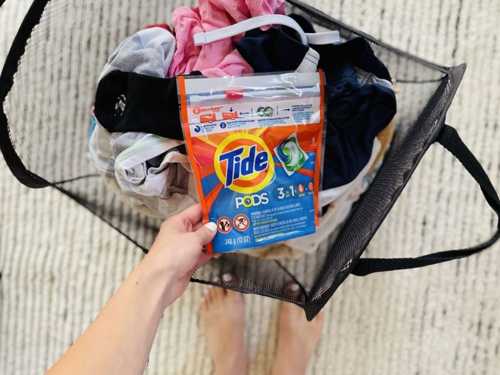 lady holding tide pods in front of her laundry