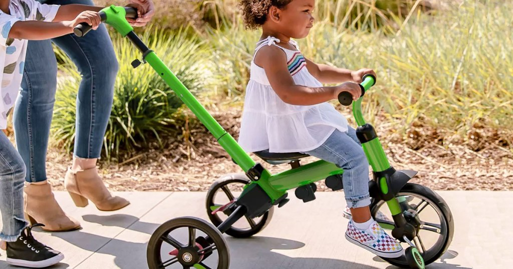 toddler girl on green push trike