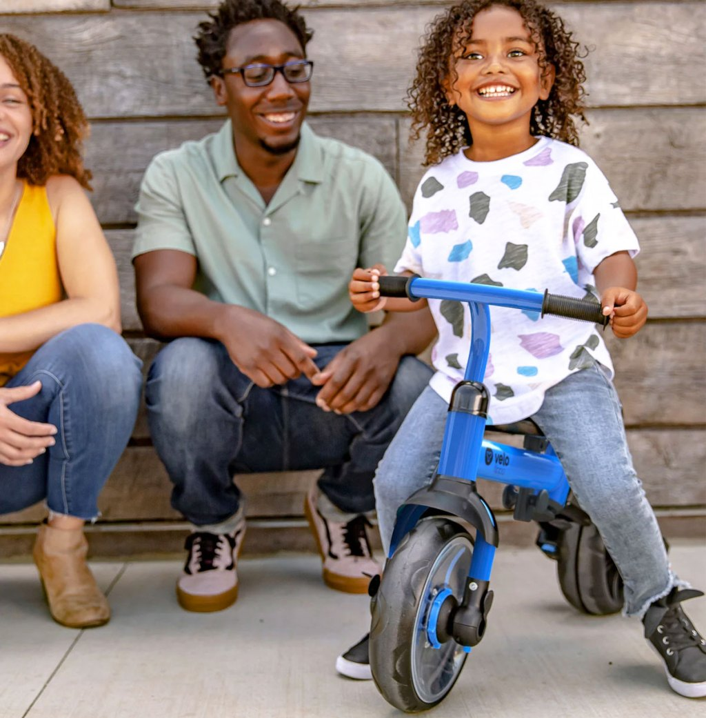 boy on blue tricycle in front of parents