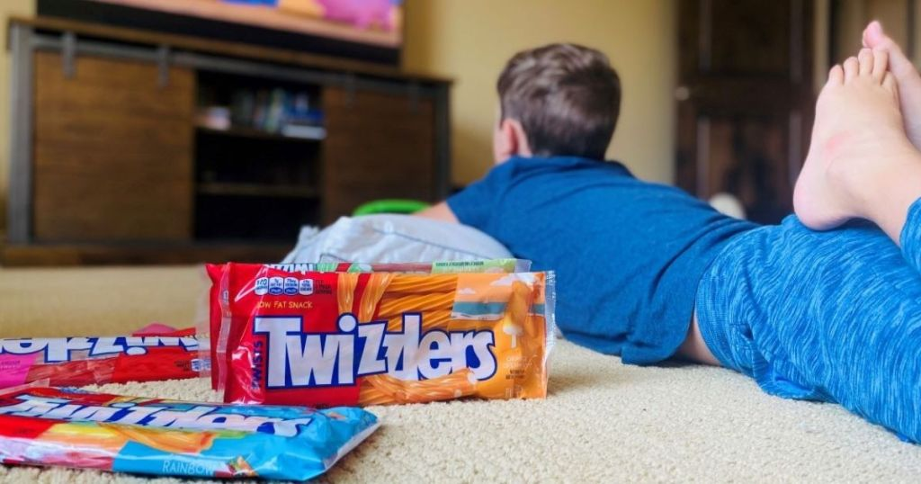 child watching a movie with Twizzlers