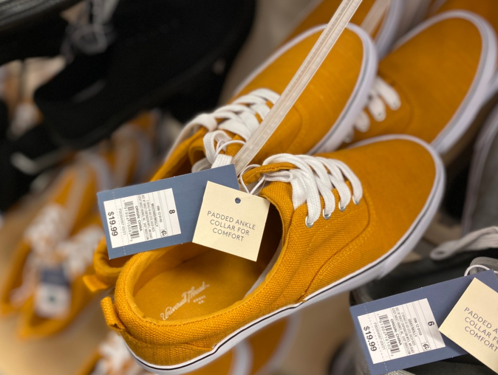 mustard colored sneakers on hanger on display in-store