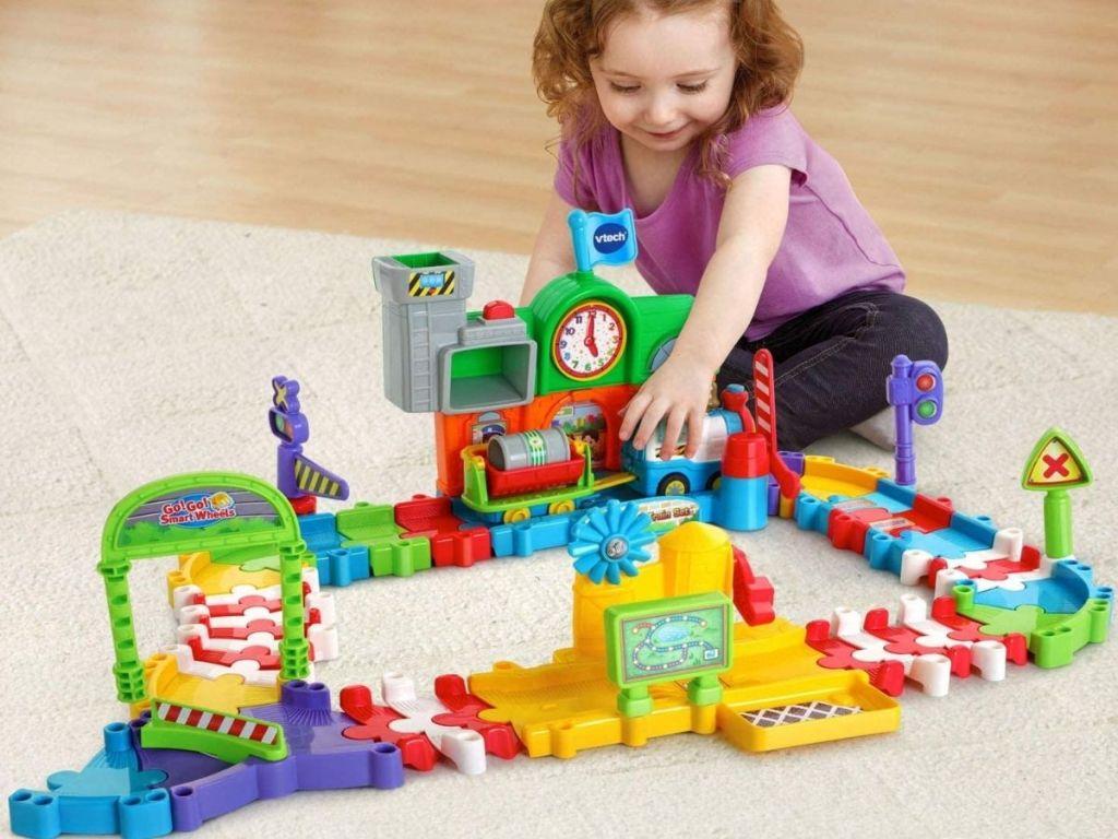 Little girl playing with VTech Go! Go! Smart Wheels Roadmaster Train Set