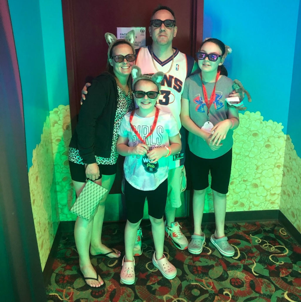 family of four standing together in neon colored room wearing sunglasses