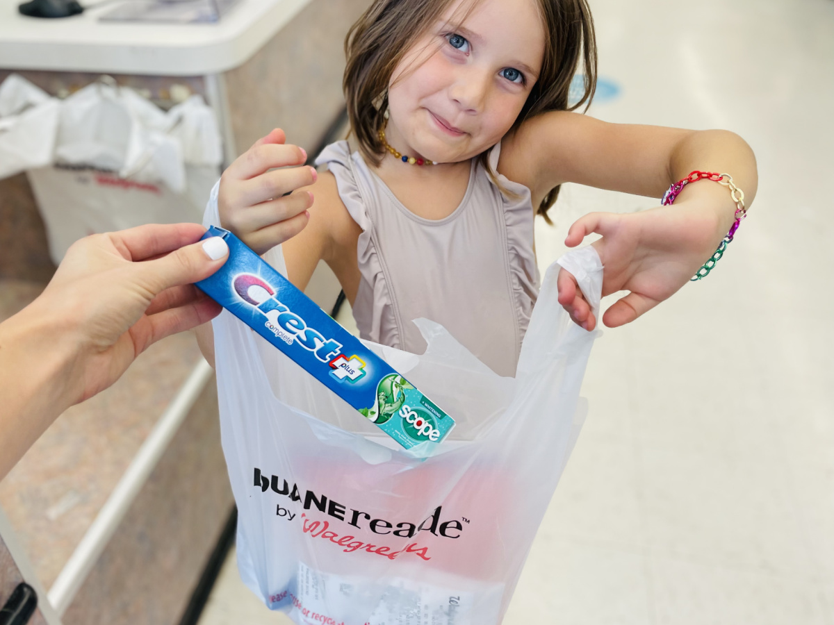 child holding up Walgreens bag in-store