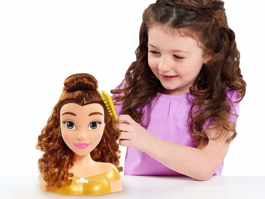 little girl playing with disney belle doll head