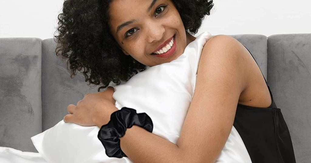 woman holding pillow and wearing scrunchie