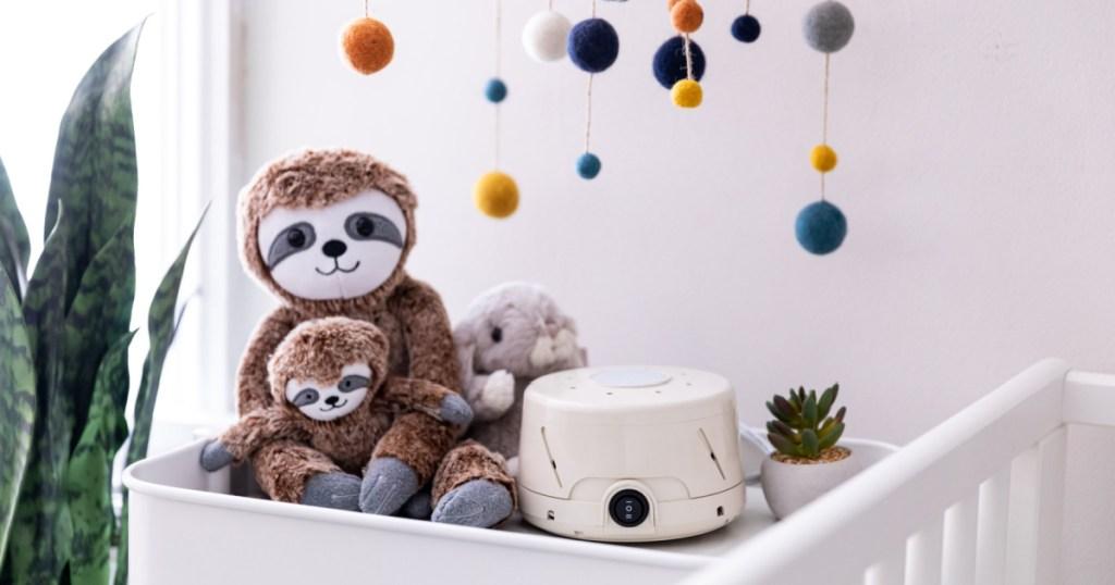 white noise machine next to plush sloths