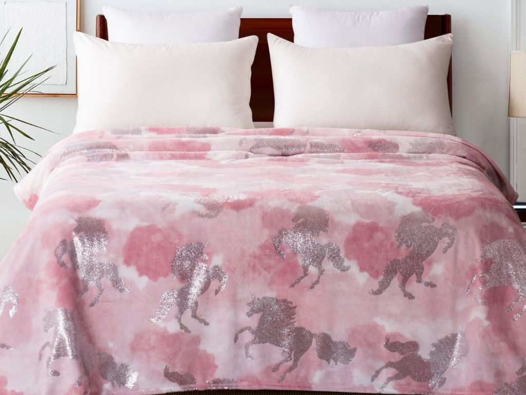 bed with unicorn blanket on it