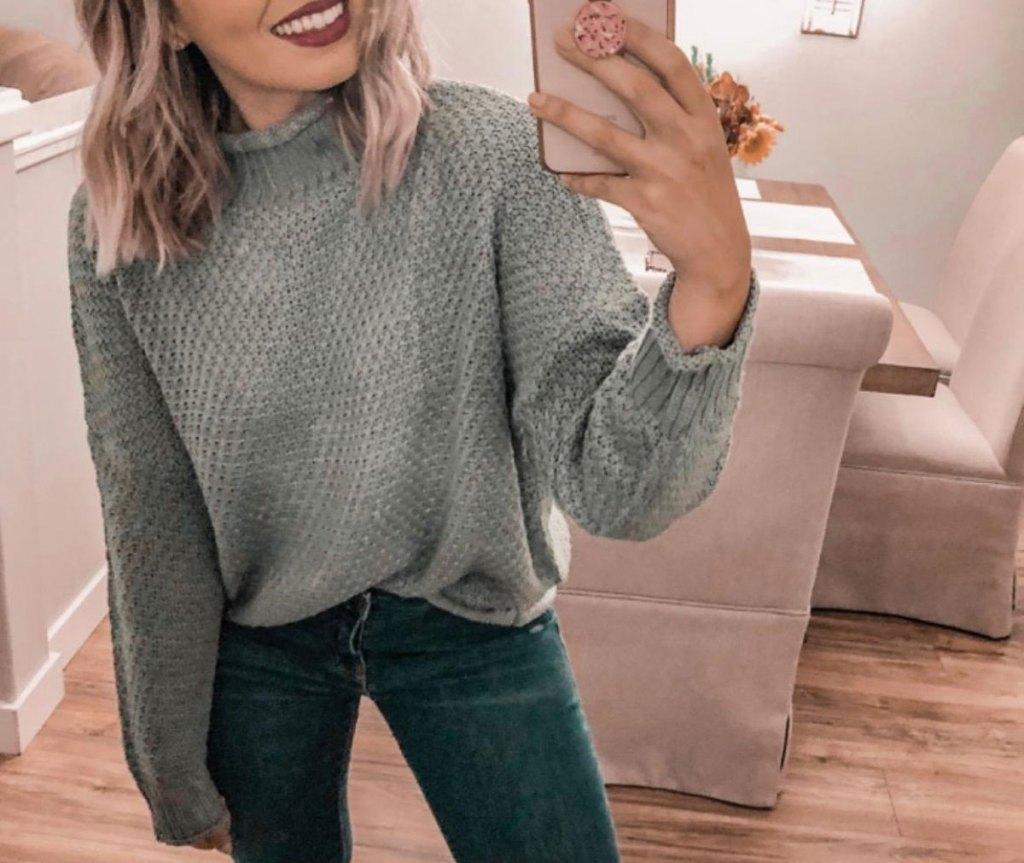 woman in gray sweater taking selfie
