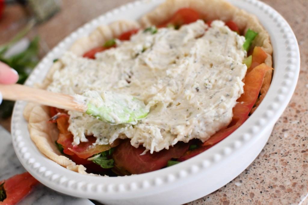 adding mayo and cheese to tomato pie
