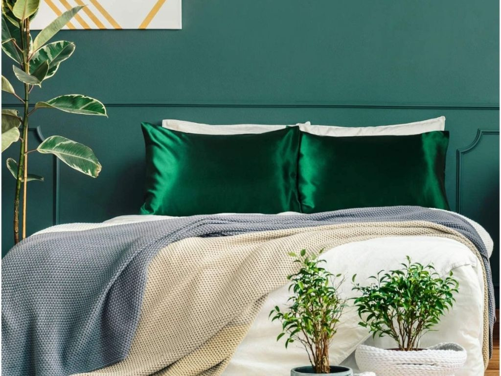green satin pillowcases on bed