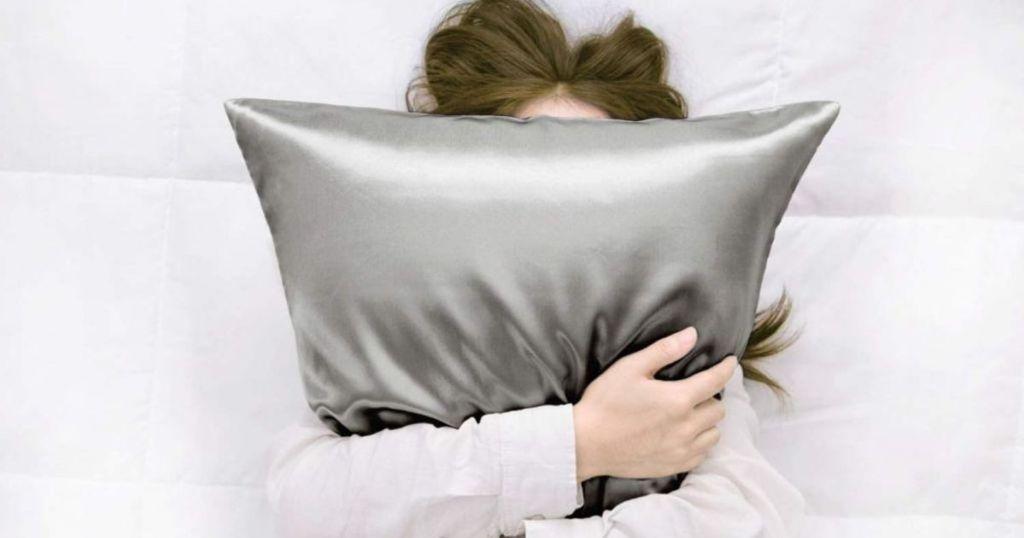 woman hugging gray satin pillow
