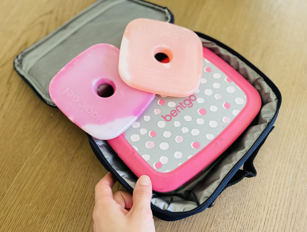 hand holding corner of lunch box with bentgo box and ice packs inside