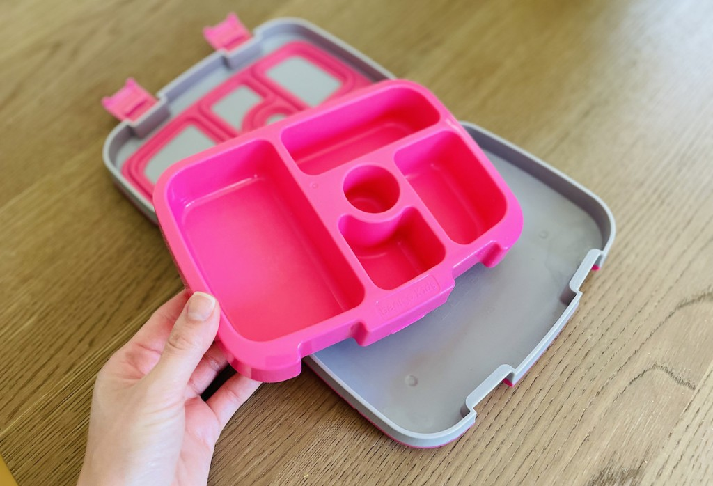 hand holding pink tray from bento box