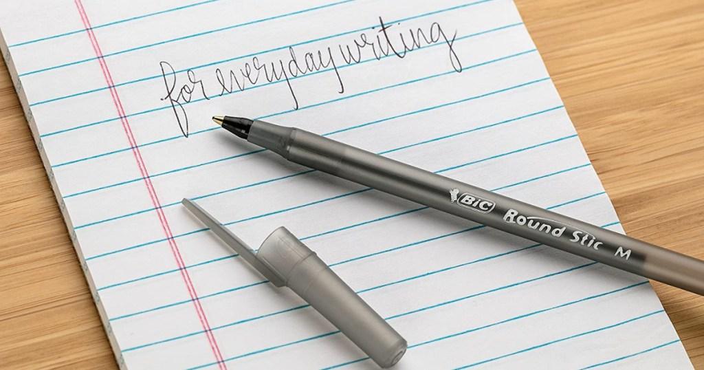 open pen sitting on writing pad