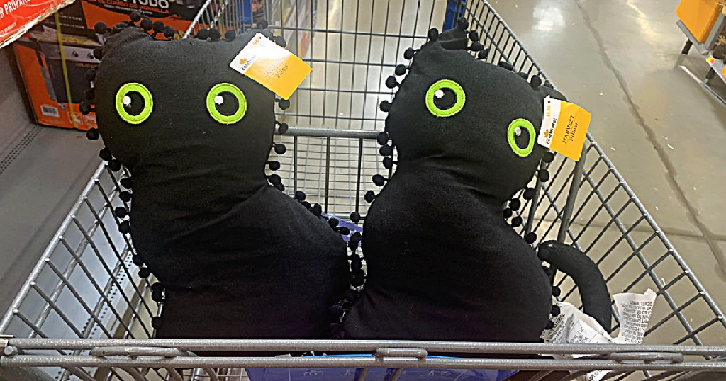 two black cat shaped throw pillows in a store shopping cart basket