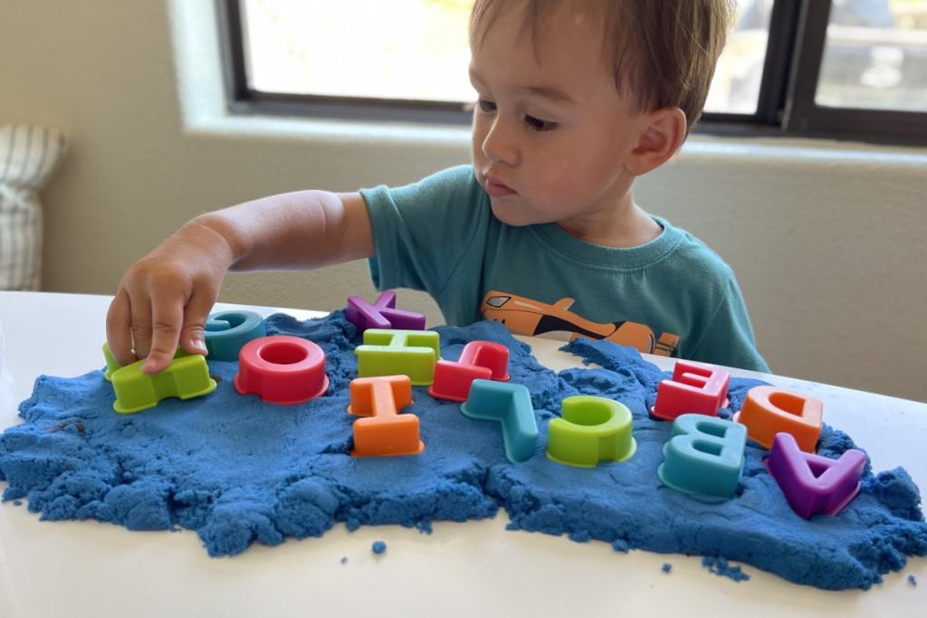 boy playing letters in kinetic sand