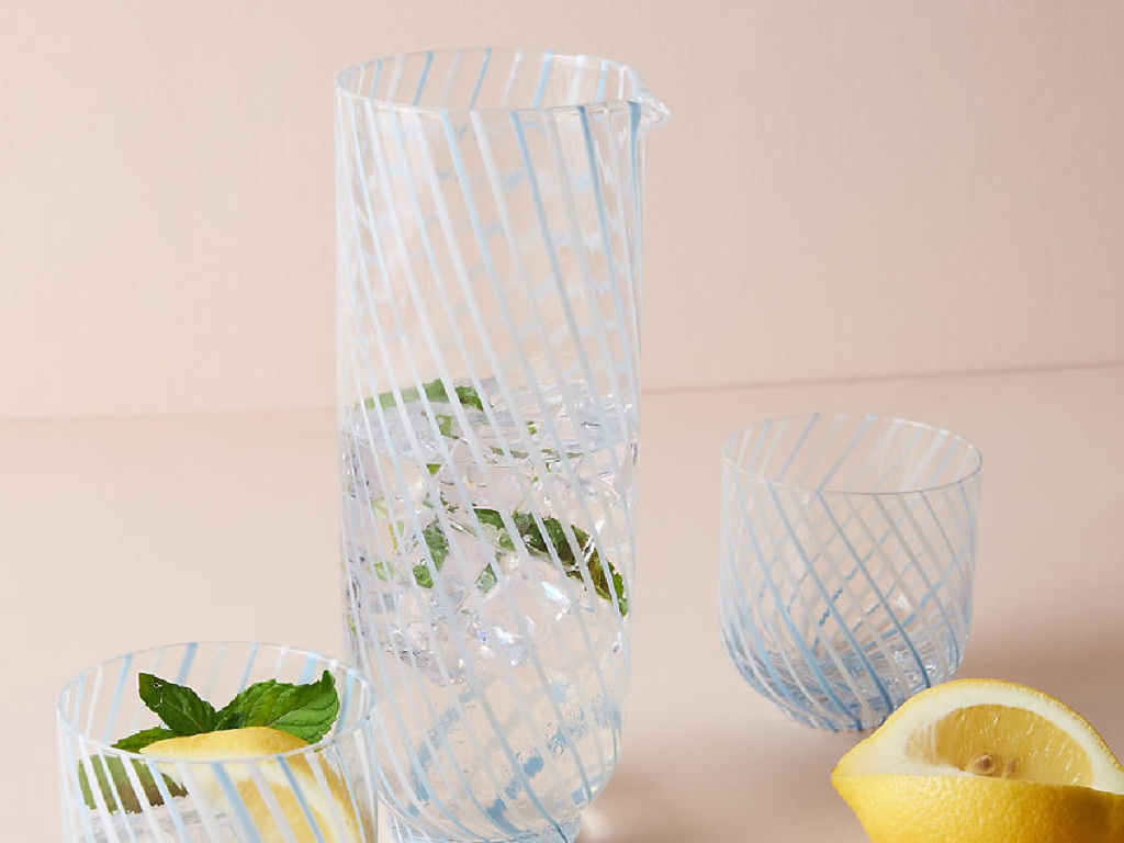 glass picther with water, lemons and glasses around it
