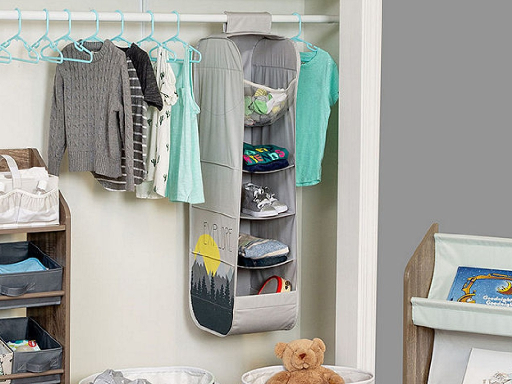 closet with clothes hanging and basket organizer