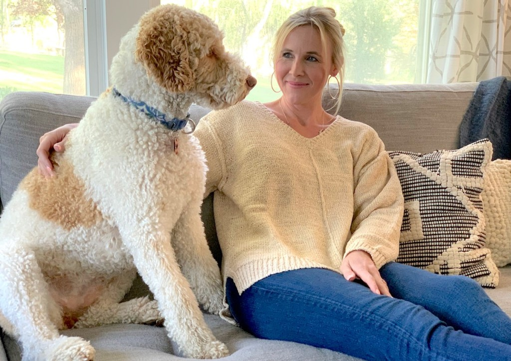 woman and dog sitting on couch in front of large window