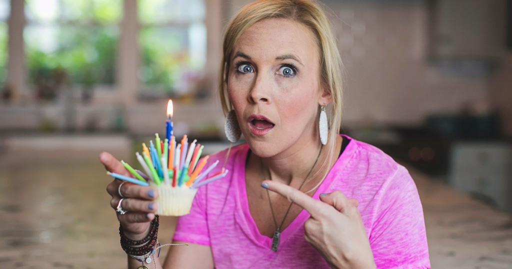 woman holding cupcake with tons of candles on top