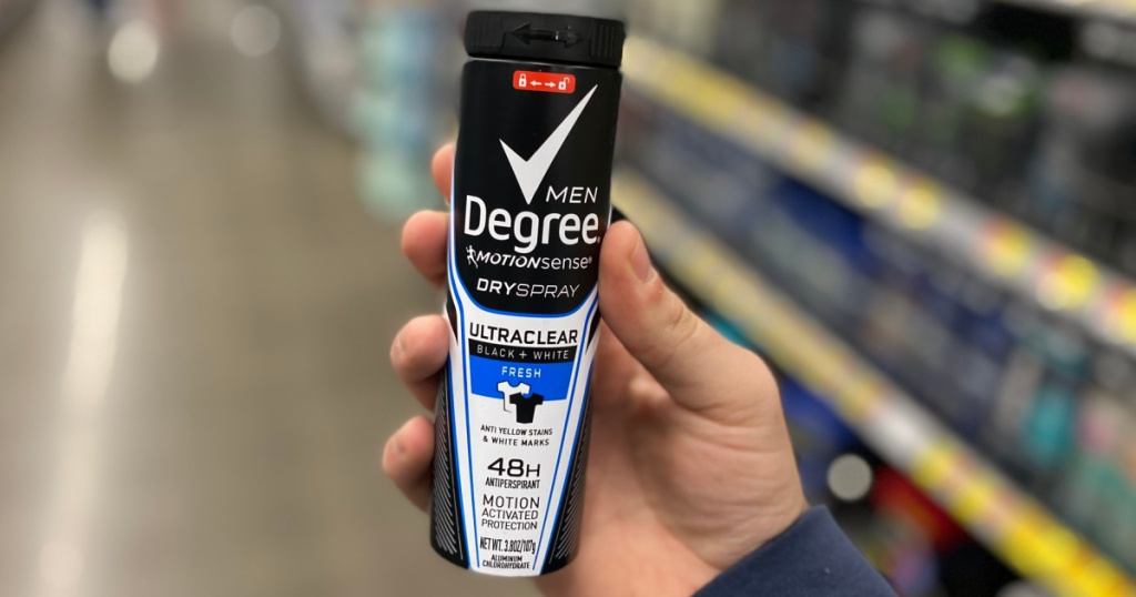 hand holding bottle of men's deodorant spray in store