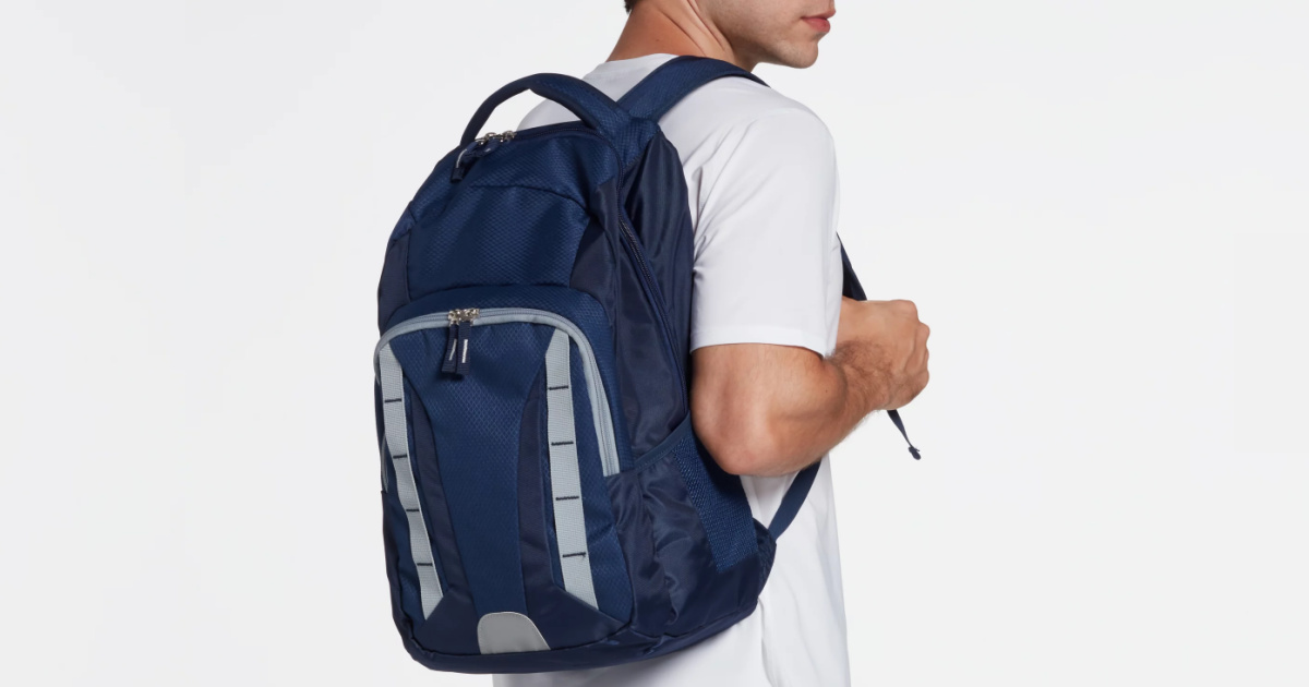 boy standing back to with a navy blue backpack over his shoulder