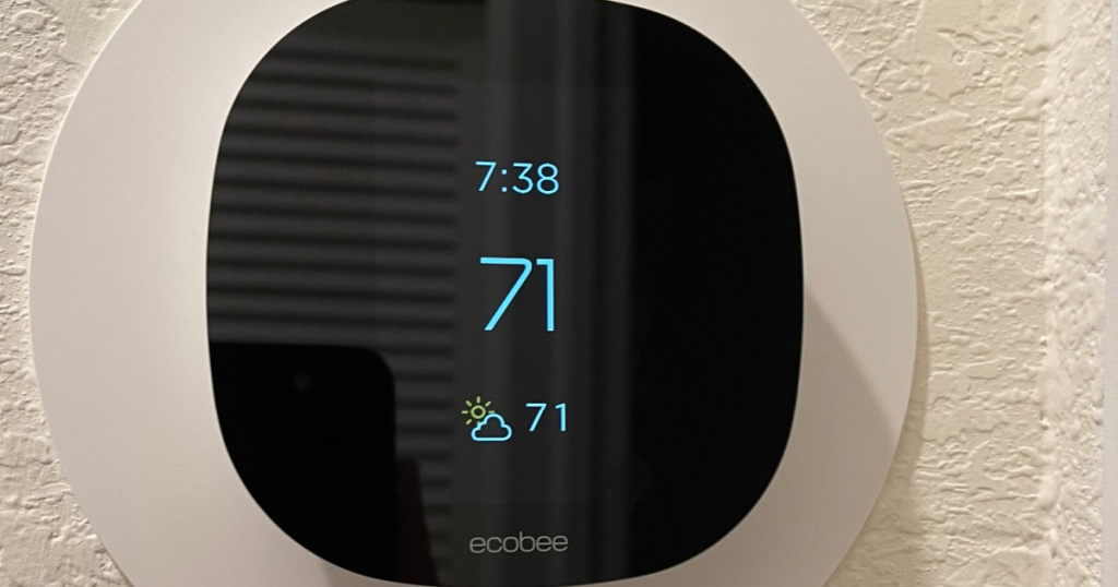 black thermostat displaying temperature on the wall
