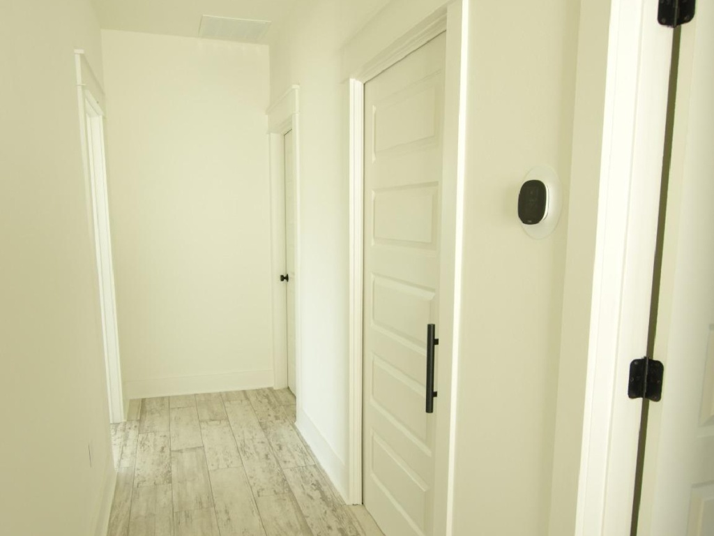 well lit hallway showing thermostat on wall