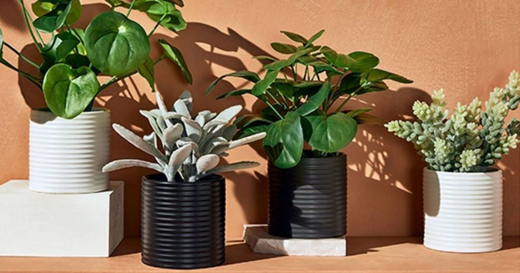 faux plants in black and white ribbed pots