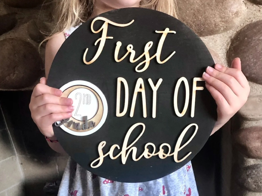kid holding first day of school sign
