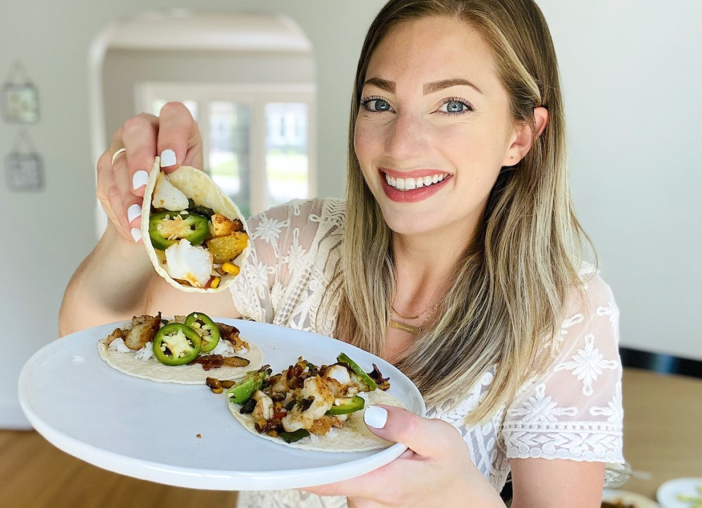 woman holding up fish taco on white plate