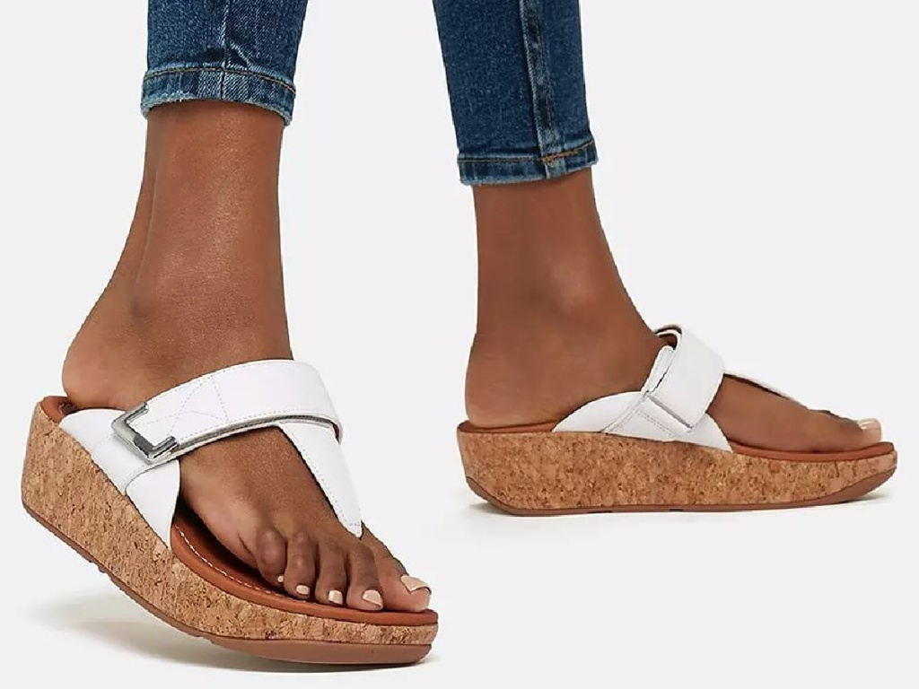 woman's feet with white sandals on